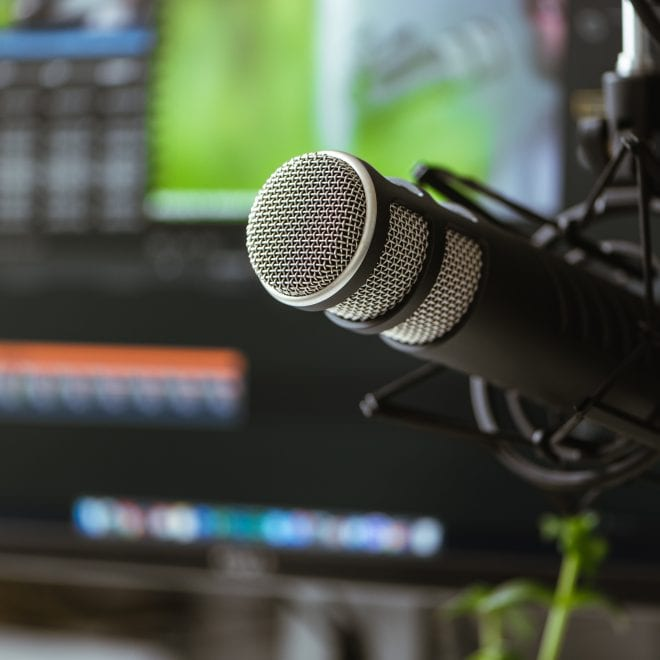 Microphone in the foreground. Blurred background. Software for recording and editing sounds. Post production.